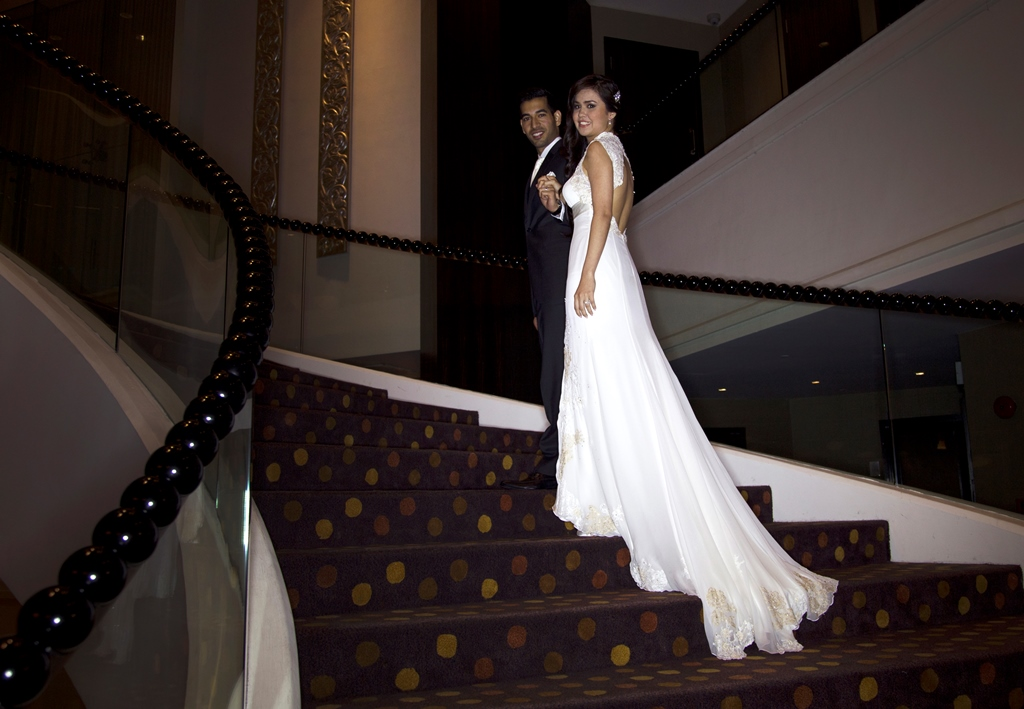 happy bride and groom smiling on stairs